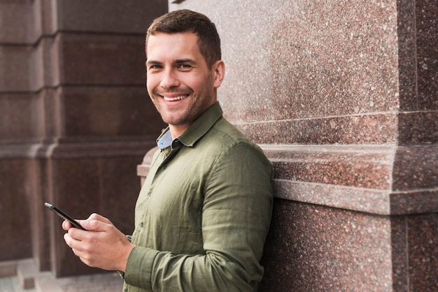 Smiling man leaning on wall holding cellphone and looking at camera Free Photo