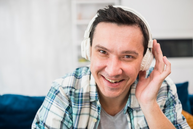 Smiling man listening music in headphones on sofa Free Photo