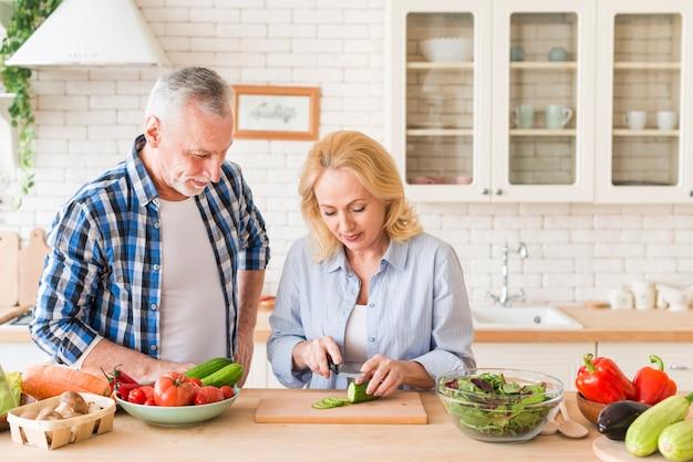 台所のテーブルの上にナイフでキュウリを切る彼女の妻を見て笑みを浮かべて男 無料写真
