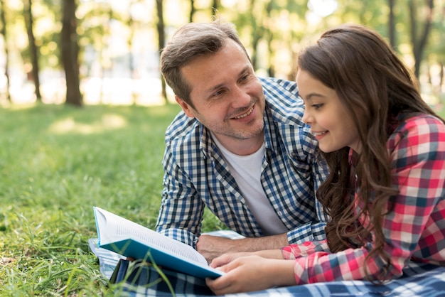 Smiling man looking at his daughter reading book lying on blanket Free Photo