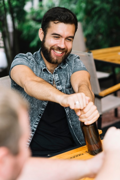Smiling man opening the alcohol bottle sitting in the restaurant Free Photo