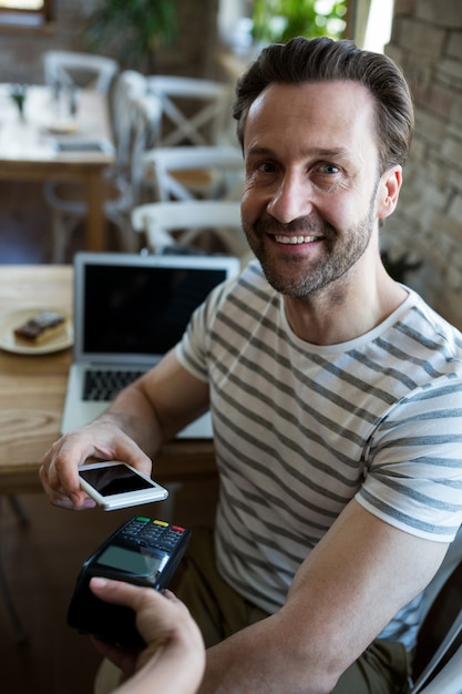 Smiling man paying with nfc technology on mobile phone Free Photo