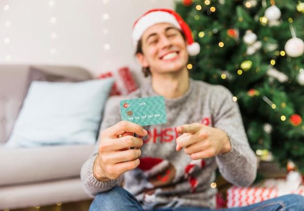 Smiling man pointing at credit card Free Photo