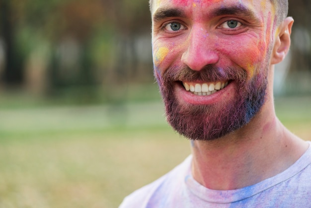 Smiling man posing with painted face at holi Free Photo