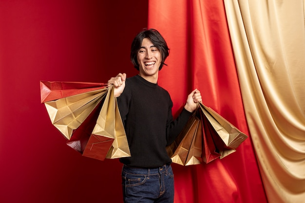 Smiling man posing with shopping bags for chinese new year Free Photo
