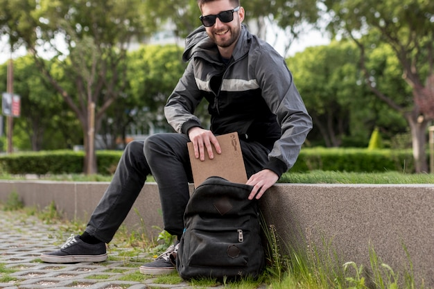 Smiling man putting book in backpack Free Photo