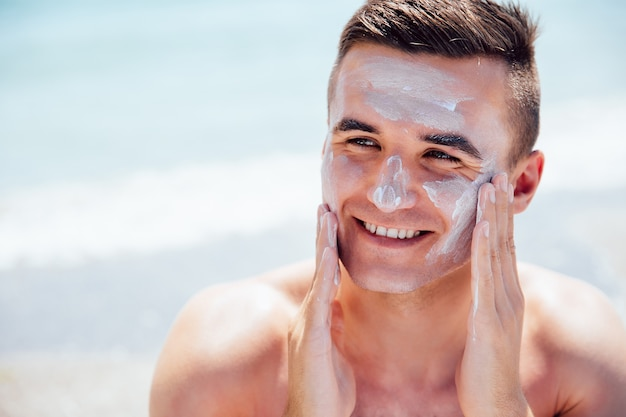 Smiling man putting tanning cream on his face, takes a sunbath on the beach. Free Photo