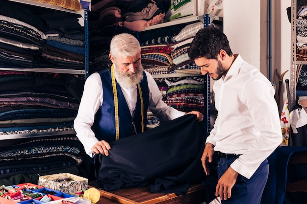 Smiling man seller displaying blue fabrics to young customer in textile shop Free Photo