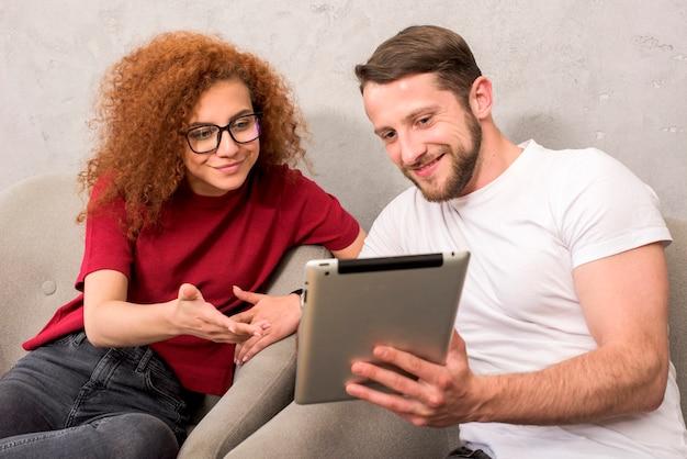 Uomo sorridente che mostra qualcosa al suo amico sulla compressa digitale Foto Gratuite