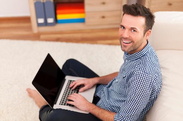 Uomo sorridente che si siede sul pavimento con il computer portatile Foto Gratuite