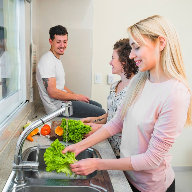 Smiling man sitting on kitchen worktop looking at two women cleaning the lettuce Free Photo
