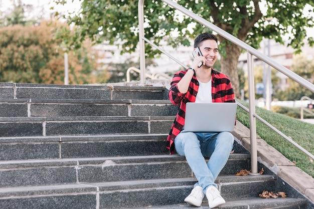 Smiling man sitting on stairway talking on smartphone Free Photo
