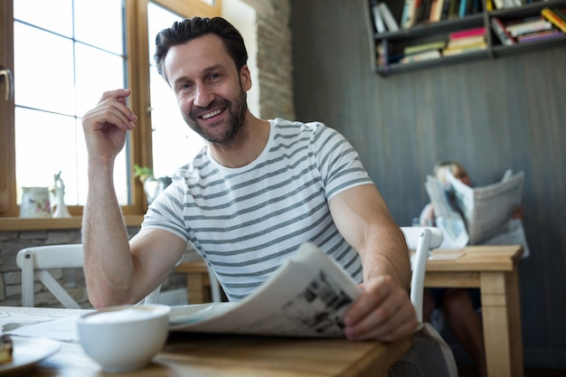Smiling man sitting with a newspaper in coffee shop Free Photo