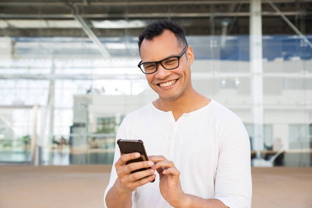 Smiling man standing at office building, holding phone in hands Free Photo