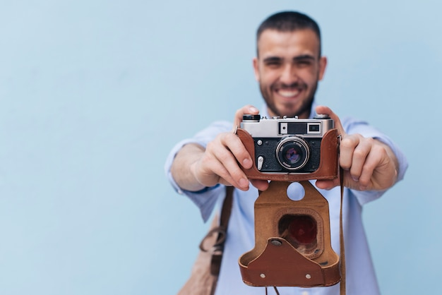 Smiling man taking photo with retro camera standing against blue wall Free Photo
