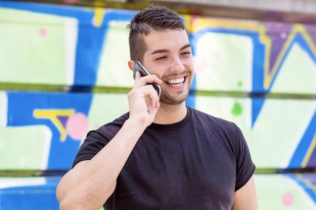Uomo sorridente che comunica sul suo telefono Foto Gratuite