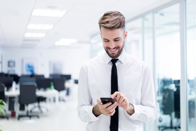Smiling man typing on his phone Free Photo