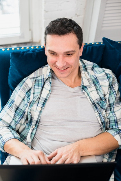 Smiling man typing on laptop and sitting on settee Free Photo