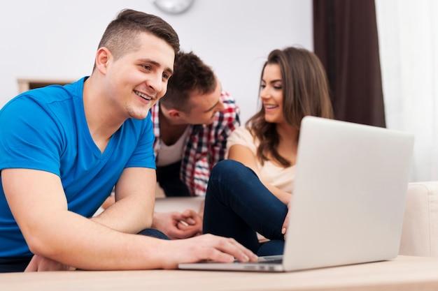 Улыбающийся человек, используя ноутбук с друзьями дома Бесплатные Фотографии