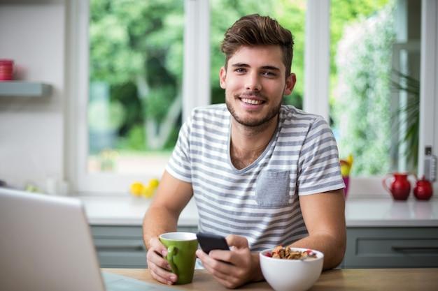 Smiling man using phone while having coffee Premium Photo