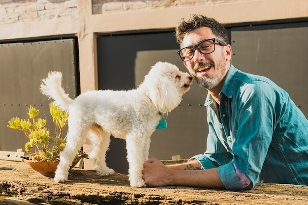 Smiling man wearing eyeglasses playing white puppy Free Photo