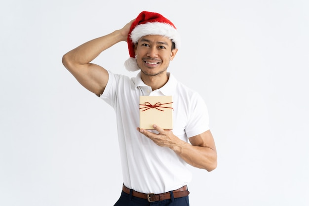 Smiling man wearing santa hat and holding gift box Free Photo