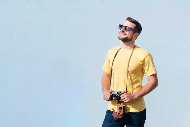 Smiling man wearing sunglasses holding camera and looking away Free Photo
