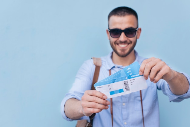 Smiling man wearing sunglasses showing air ticket on blue background Free Photo