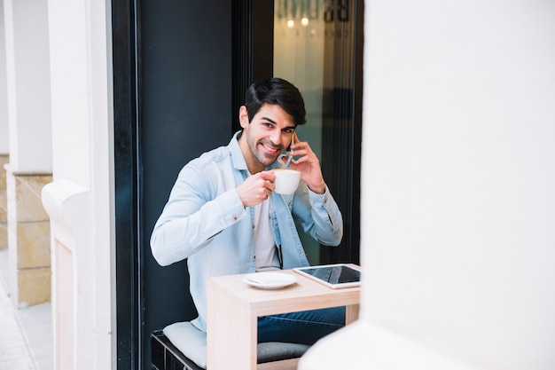 Smiling man with cup talking on smartphone Free Photo