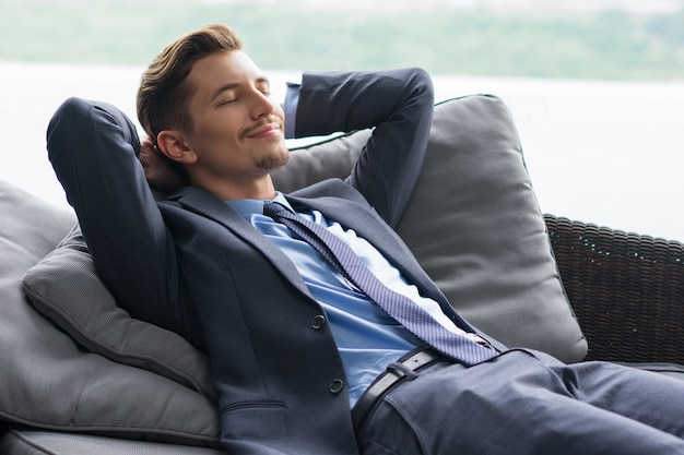 Smiling Man with Hands Behind Head Dozing on Couch Free Photo