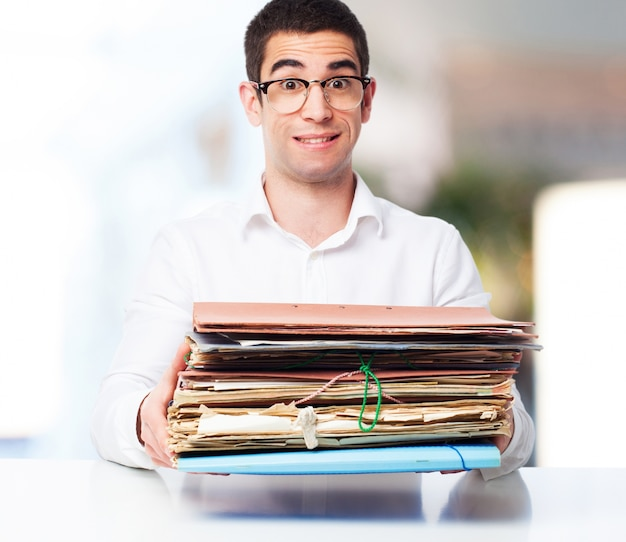 Smiling man with a pile of papers in hands Free Photo