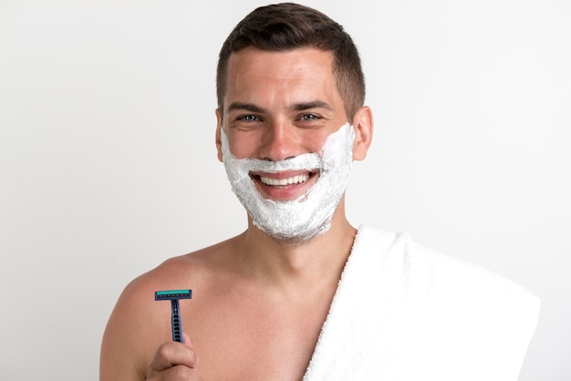 Smiling man with towel applied shaving cream holding razor looking at camera Free Photo