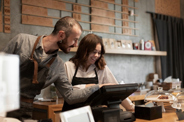 Smiling man and woman at cash register Free Photo