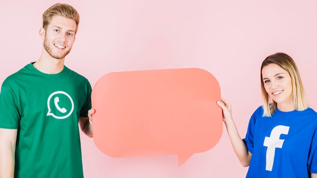 Smiling man and woman holding empty orange speech bubble Premium Photo