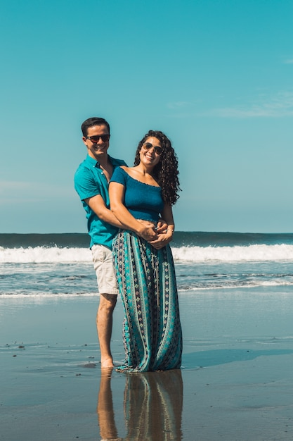 Smiling man and woman hugging on waterfront of beach Free Photo