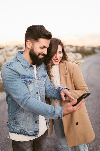 Smiling man and woman looking on phone on road Free Photo