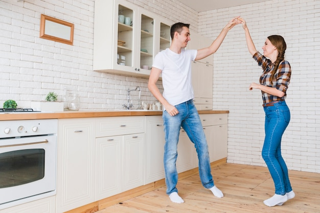 Smiling man and woman in love dancing in kitchen Free Photo