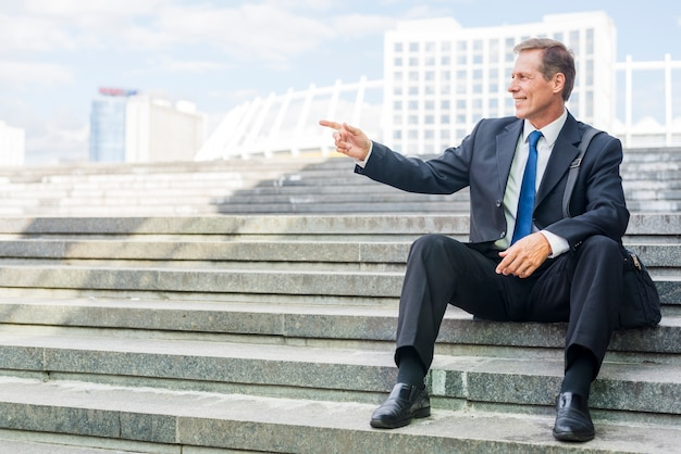 Smiling mature businessman pointing at something while sitting on staircase Free Photo