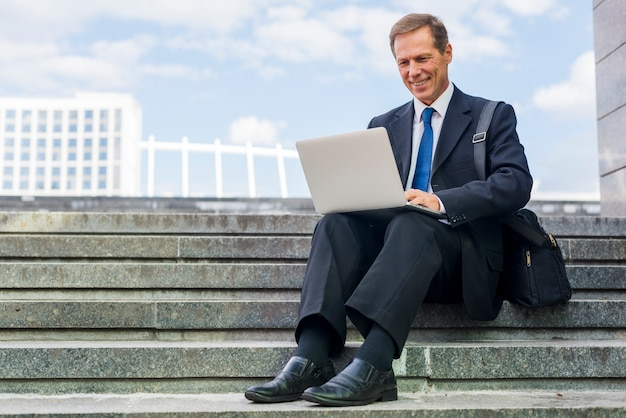 Smiling mature businessman sitting on staircase working on laptop Free Photo