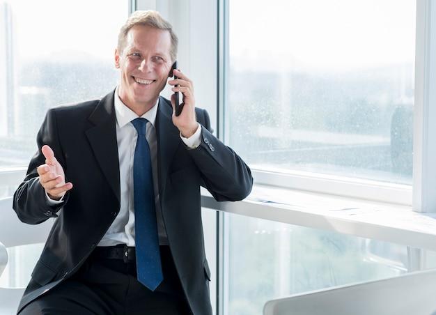 Smiling mature businessman talking on mobile phone Free Photo