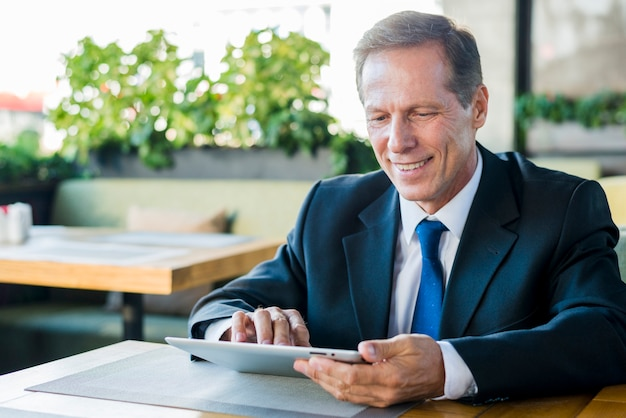 Smiling mature businessman working on digital tablet in restaurant Free Photo