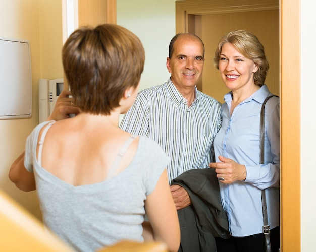 Smiling mature family couple visiting daughter Free Photo