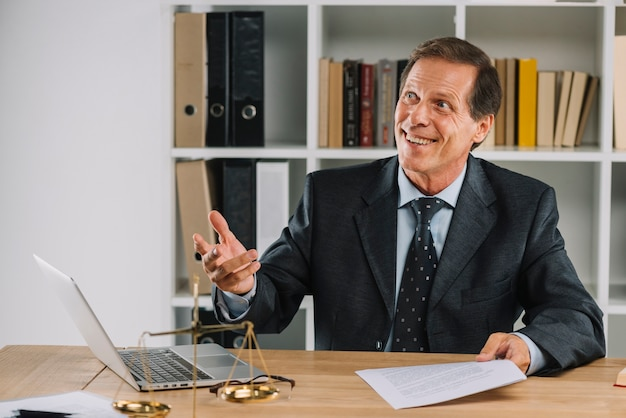 Smiling mature lawyer holding document in hand at workplace Free Photo