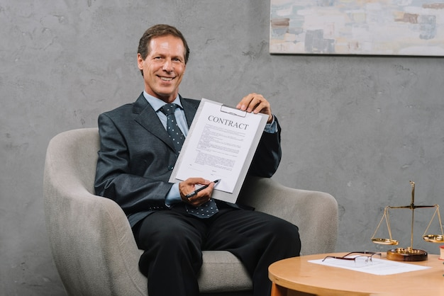 Smiling mature lawyer holding pen pointing at signature place on a contract document Free Photo