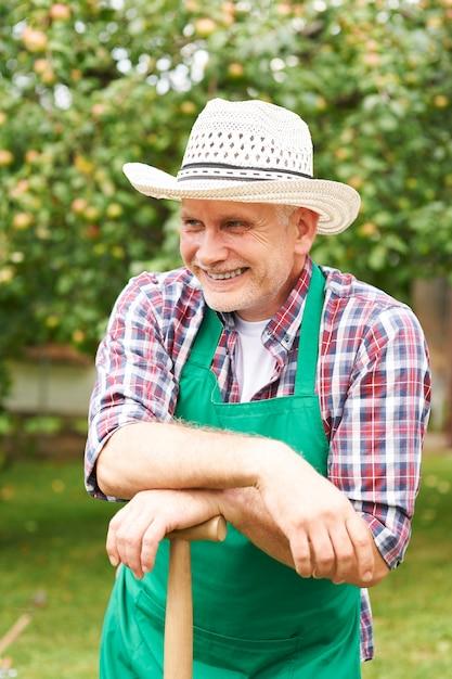 정원 작업 중 웃는 성숙한 남자 무료 사진