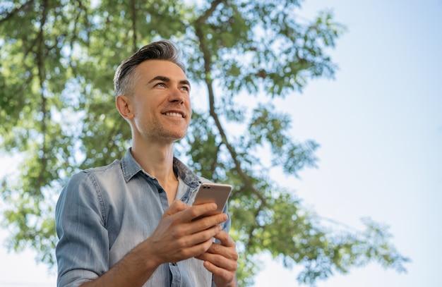 Smiling mature man using mobile phone, shopping online. Premium Photo