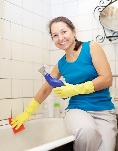 Smiling  mature woman cleans bathtub Free Photo