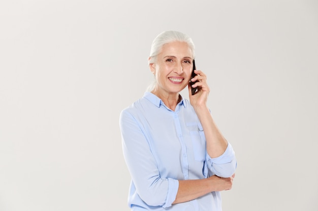 Smiling mature woman talking on smartphone isolated Free Photo