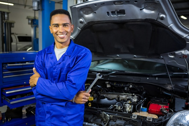 Smiling mechanic with arms crossed and spanner Free Photo