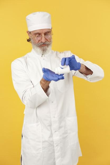 丸薬で笑顔の医師。孤立。青い手袋をはめた男。 無料写真
